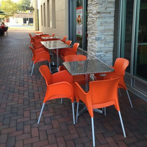 orange outdoor armchairs and silver tables
