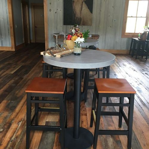 concrete bar table tops and black barstools with wooden saddle seat