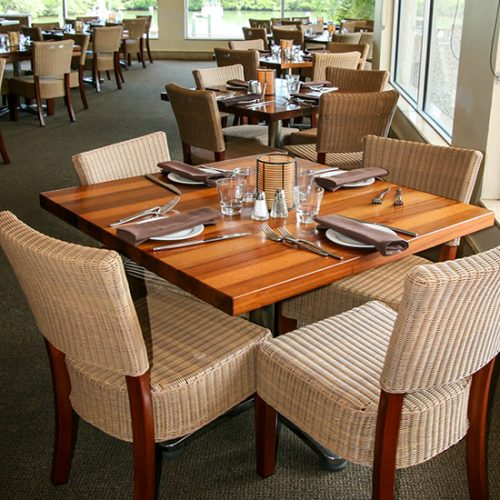 wood table and wicker chairs in restaurant